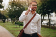 Businessman talking on mobile phone walking in street