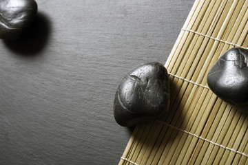 Schieferplatte mit Steinen und Bambusmatte