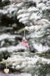 Nice decorations on a Christmas tree with snow outdoors. Celebration, winter and holidays concept