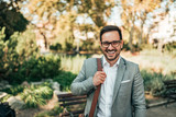 Portrait of a modern business man outdoors. Smiling and looking at camera. - 227637442