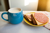Milk and sandwiches on the table in the morning, simple breakfast - 227639605