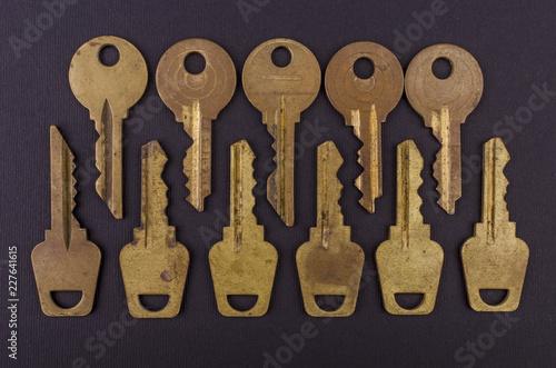 Foto Murales Old vintage keys on black background. Several types of old retro keys. Set of old keys. Composition of different keys.