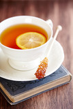 Cup of Tea with Lemon and brown Sugar Stick  on a old Book. Symbolic image. Rustic wooden background.  - 227641806