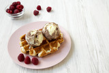 Traditional belgian waffle with icecream and raspberries on pink plate, side view. White wooden background. Copy space.