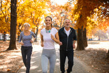 Senior man and woman and young female instructor  workout on fresh air. Outdoor activities, healthy lifestyle, strong bodies, fit figures. Stylish, modern sportswear. Different generations - 227646801