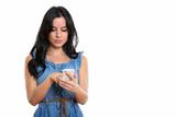 Studio shot of young beautiful Spanish woman using mobile phone - 227647847