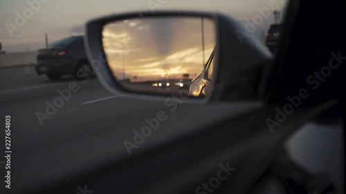 The day is coming to an end as the sun sets and seen through the rear view mirror