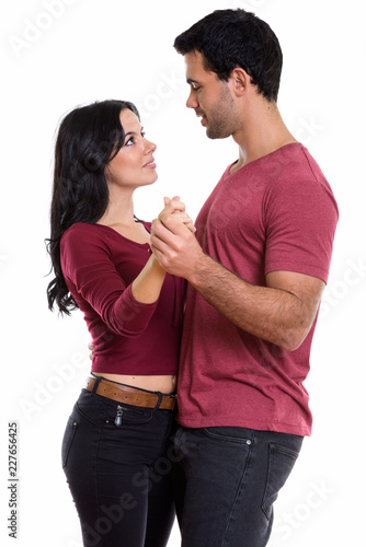 Studio shot of young happy couple smiling while dancing and look - 227656425