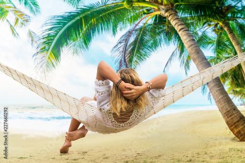 Leinwandbild Motiv Woman sitting in hammock on the beach.