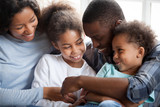 Close up black african loving family with small children have a fun sitting on couch together at home. Funny playful american married couple two little preschool adorable daughter and son communicate