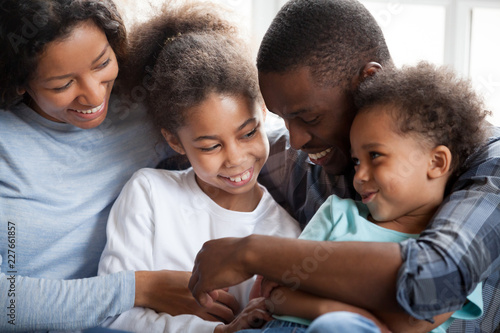 Leinwandbild Motiv Close up black african loving family with small children have a fun sitting on couch together at home. Funny playful american married couple two little preschool adorable daughter and son communicate