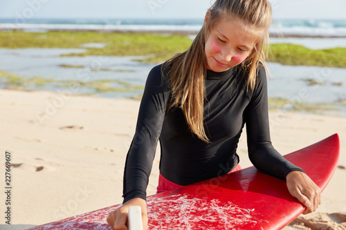 Fototapeta Cropped shot of attractive woman uses wax for safe surfing, has appealing appearance, dressed in wetsuit, poses on beach near bay, recreats in tropical country. Extreme sport and lifestyle concept