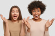 Photo of emotive females gesture with palms, react to awesome news, meet foreign friend, isolated over white background. Amazed dark skinned young woman has Afro haircut spends free time with fellow