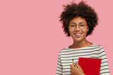 Studio shot of pretty dark skinned girl with gentle smile, prepares for classes, carries red notepad and pencil, wears round glasses, isolated over pink background, free space for your advertisement - 227672824