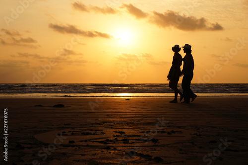 Foto Murales Silhouettes of walking people on sunset background on Arambol beach, India, Goa