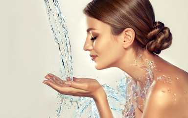 Beautiful spa woman with water splashes. Moisturizing facial skin, beauty and care. © Sofia Zhuravetc
