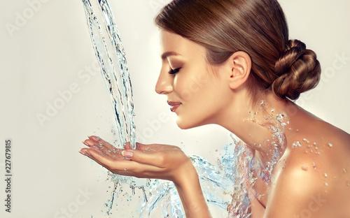 Piękna zdrój kobieta z wodnymi pluśnięciami. Nawilżająca skóra twarzy, uroda i pielęgnacja.