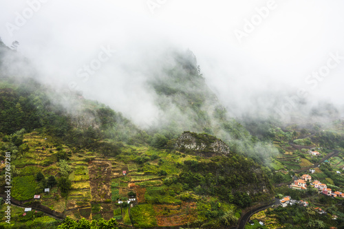 Foto Murales Low clouds over the mountain village.