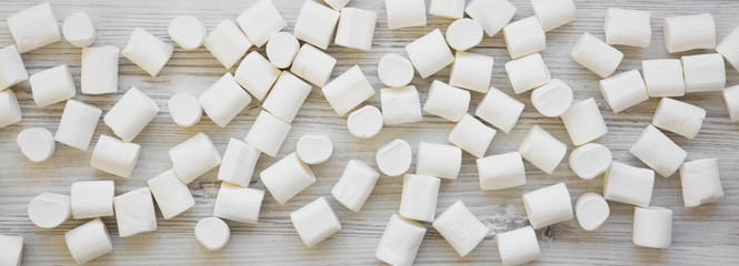 Sweet white marshmallows on a white wooden table, overhead view. Flat lay, from above, top view. Close-up. © Liudmyla