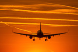 Airplane prepare for landing at sunset with beautiful red sky in background - 227691681