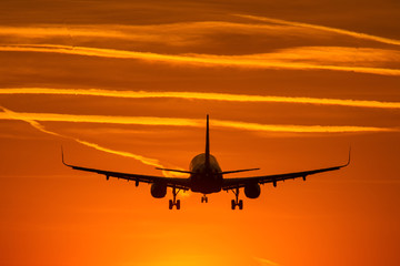 Airplane prepare for landing at sunset with beautiful red sky in background