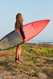 People, resort, recreation. Full length shot of brave girl ready to hit waves for first time, carries surfboard with fixed legrope serves as connection to board, has thoughtful look at peaceful ocean - 227703051