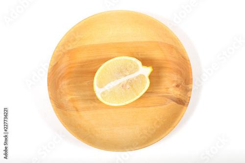 Foto Murales лимон половинка лежит на тарелке из дерева