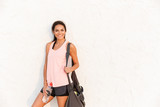 Photo of athletic woman in sportswear with sporty bag, smiling and standing outdoor over wall - 227741697