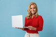 Portrait of charming blond woman 20s holding silver laptop, isolated over blue background in studio