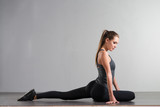 athletic fitness young woman doing sports exercises on a gray background