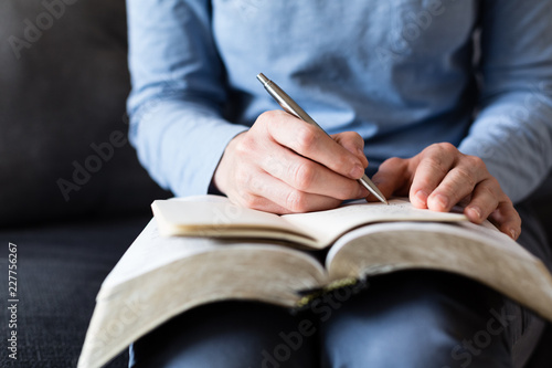 Bible Study - Woman Taking Notes as She Reads from an Open Bible