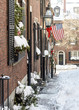 USA, Boston - January 2018 - Acorn Street in the snow with the American flag flying