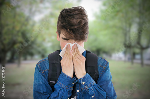 Foto Murales young with a scarf sneezing with cold or flu symptoms