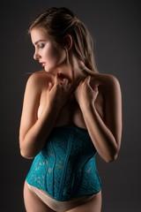 Slim blonde in corset in the dark profile view