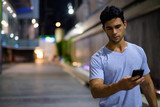 Young handsome Hispanic man exploring the city streets at night - 227769065