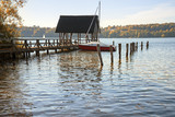 boathouse with jetty and sailing boat in the lake on a sunny autumn day, copy space - 227771411