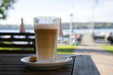 latte macchiato in an open air cafe at the lake, copy space - 227771462