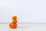 Jack-o-lantern carved pumpkin on light wall background with copy space, autumn and halloween home decor - 227771675