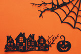 Halloween holiday concept. haunted village over orange background. Top view, flat lay.