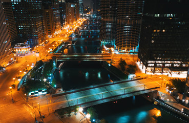 Chicago River with boats and traffic in Downtown Chicago at night