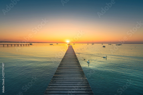 Acrylglas Pier Garda lake, swans and jetty, sunset view from Pacengo Lazise. Italy