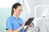 Dentist consulting online information in a tablet
