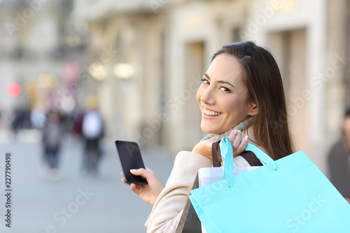 Leinwanddruck Bild Happy shopper holding phone and shopping bags