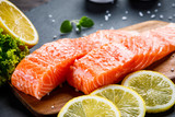 Fresh raw salmon fish served on black stone on wooden table - 227791445