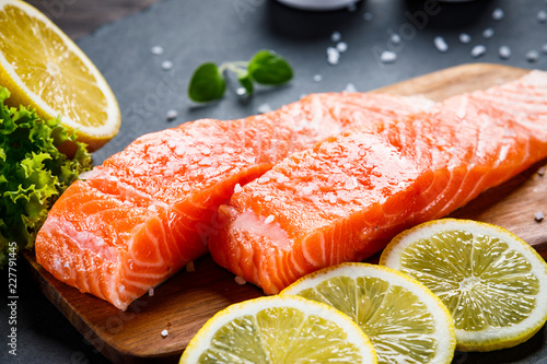 Leinwandbild Motiv Fresh raw salmon fish served on black stone on wooden table