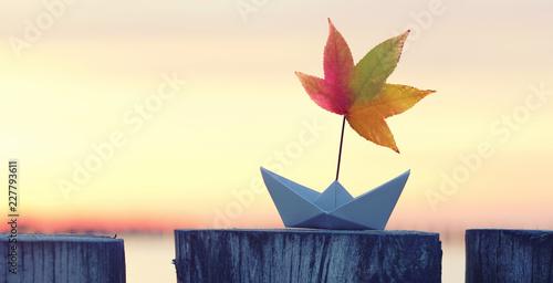 Leinwandbild Motiv Papierboot mit bunten Laubblatt als Segel - Herbst