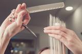 Hairdresser is cutting long hair in hair salon - 227795256