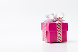 Pink color gift box tied with white red stripe ribbon isolated on white background - 227797205