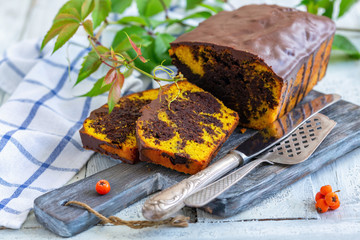 Sliced marble cake with chocolate icing.