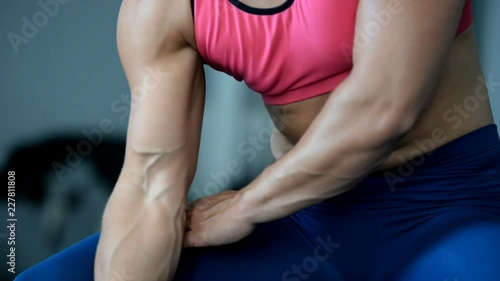 Sticker A woman athlete trains biceps dumbbells in the gym.